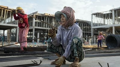 Cambodian women carry heavy load on construction sites