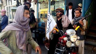 A Taliban fighter sits on his motorcycle adorned with a Taliban flag on a street in Kunduz, Afghanistan [AP]
