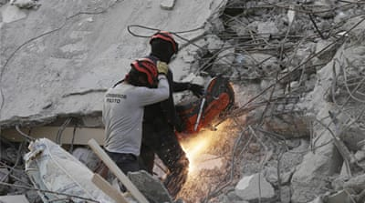 A rescue team member cuts an iron rod at a collapsed hotel in Pedernales, Ecuador [Henry Romero/Reuters]