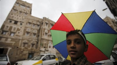 A boy with an umbrella hat walks in an old quarter of Yemen's capital Sanaa [Reuters]