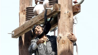 The man climbed an electricity pole and forced himself into a makeshift noose made of a scarf [Giorgos Moutafis/Reuters]