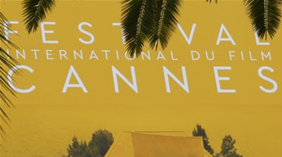Palm fronds frame a giant canvas of the official poster of the 69th Cannes Film Festival in Cannes, France [Reuters]