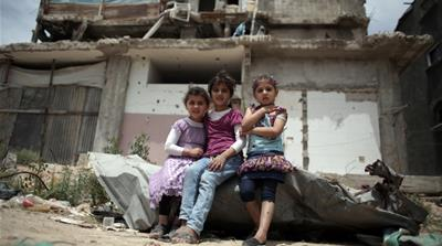 Palestinian girls sit in front of a destroyed house in Shijaiyah neighbourhood in eastern Gaza City [AP] [The Associated Press]