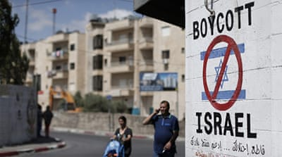 Palestinians walk past a sign painted on a wall in the West Bank biblical town of Bethlehem [Getty]