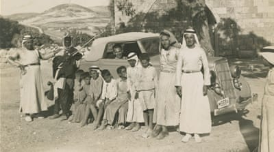 Men and children take a photo with one of the first cars to enter the village of Sabastia, Nablus, 1940-1959 [From the family album of Madhat Kayed/The Palestinian Museum]