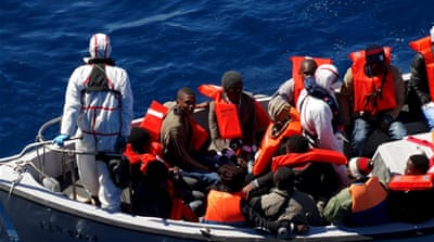 Refugees sit on a boat during a rescue operation by Italian Navy vessels last March [Reuters]