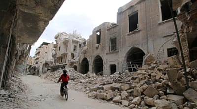 A boy rides a bicycle near damaged buildings in the rebel held area of Old Aleppo, Syria [REUTERS]