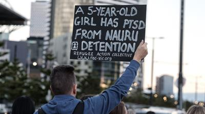Protesters from the Refugee Action Collective demand the closure of refugee prison camps on Nauru and Manus Islands in Melbourne [Luis Ascui/Getty]