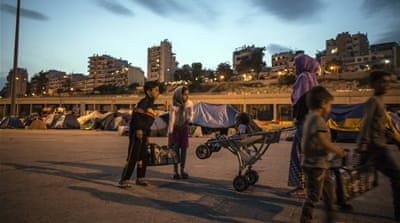 A family of Syrians collect supplies against a background of the multi-storey apartment buildings in Athens [Iason Athanasiadis]