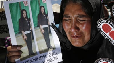 A woman holds a double image showing her late daughter, a victim of a violent crime, in La Paz, Bolivia [Juan Karita/AP]