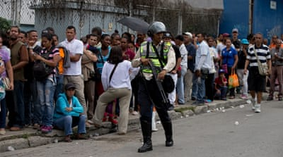Flanked by police in riot gear, people line up outside a supermarket to buy food in Caracas, Venezuela [AP Photo/Fernando Llano]