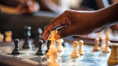 Katende advises one of his students during a match at the Katwe Chess Academy. The players range in age from five to 26 [Aurelie Marrier d'Unienville/Al Jazeera]