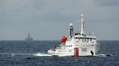 A Chinese coastguard vessel passes near a Chinese oil rig in the South China Sea [Reuters]