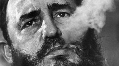 Fidel Castro exhales cigar smoke during an interview at his presidential palace in Havana, 1945 [Charles Tasnadi/AP]