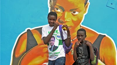 Violet Phiri and her younger brother, Mwengu, stand by a mural of Esther Phiri, the seven-time world champion, in Matero, Lusaka [Tendai Mariama/Al Jazeera]
