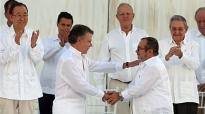 "President Santos, left, and FARC''s ""Timochenko"" shake hands after signing the peace agreement [Fernando Vergara/AP]"