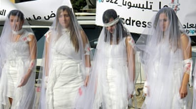 Activists from the Lebanese NGO ABAAD dressed as injured brides during a protest against the law in Beirut last month [EPA]