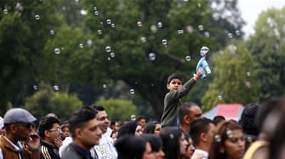 A boy sprays bubbles as people listen to music during Eid in Birmingham, central England [File: Reuters]