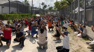 Refugees in the Manus centre protest against their detention by holding up signs [Courtesy @ManusAlert Telegram]