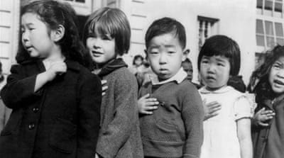 Children at the Weill public school in San Francisco pledge allegiance to the American flag in April 1942, prior to the internment of Japanese Americans [Dorothea Lange/Ceative Commons]
