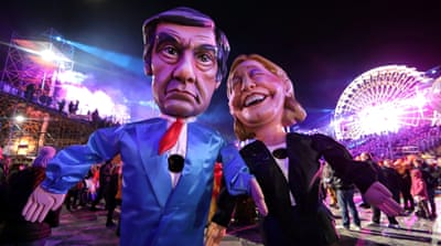 Figures of former Prime Minister Francois Fillon and French National Front leader Marine Le Pen are paraded through the crowd during the 133rd Carnival parade [Eric Gaillard/Reuters]