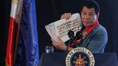 Duterte holds a compilation of pictures of people involved in the drug trade during his speech on Thursday [Reuters]