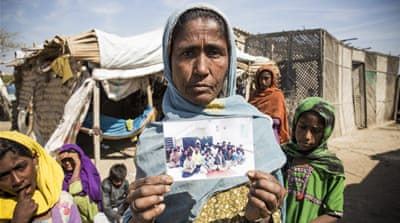 Sakina holds a photo released by Indian government agencies. In it are her nine family members who were among the 26 fishermen arrested by the Indian authorities on Dec 18 [Faras Ghani/Al Jazeera]