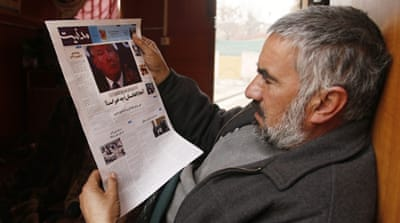 An Afghan man reads a local newspapers carrying front page news of the inauguration of US President Donald Trump in Kabul, Afghanistan, January 22 [Jawad Jalali/EPA]