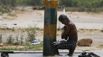 An Indian girl operates a water hand pump for her younger brother to drink on a hot afternoon on the outskirts of Jammu, Kashmir, in June 2014 [Jaipal Singh/EPA]