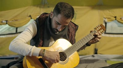 After organising the talent show, Mahmoud learned how to play the guitar. [Al Jazeera]