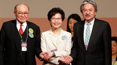 Candidates Woo Kwok-hing and John Tsang congratulated Carrie Lam (C) after the election [Bobby Yip/Reuters]