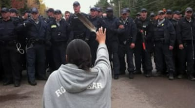 Amanda Polchies holds out an eagle feather as Royal Canadian Mounted Police crack down on a protest by Mi'kmaq people against plans to frack near Elsipogtog, New Brunswick, Canada [Al Jazeera]