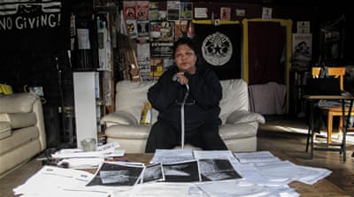 Tina McGrath sits in front of the many documents pertaining to harm she says she has suffered at the hands of the police [Creede Newton/Al Jazeera]