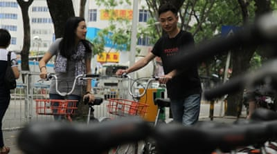 Stephanie Wong takes one of Shenzhen's dockless city cycles for a test ride [Al Jazeera]