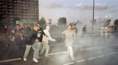 Right-wing extremists run through spray from water cannons during clashes between police and demonstrators in Rostock, Germany, on Monday, August 24, 1992 [Thomas Haentzschel/AP]