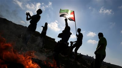 Palestinian protesters hurl stones towards Israeli troops during clashes near Gaza border [File: Reuters]
