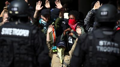 Anti-fascist protesters and bystanders hold their hands in the air while law enforcement officers detain them during competing demonstrations in Portland [David Ryder/Reuters]