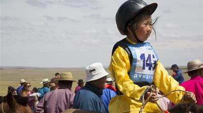 Bujinlkham Damdinsuren, nine, awaits the start of the 24km horse race atop one of her family's horses at a Naadam festival in Tsagaandelger, Mongolia [Hannah Griffin/Al Jazeera]