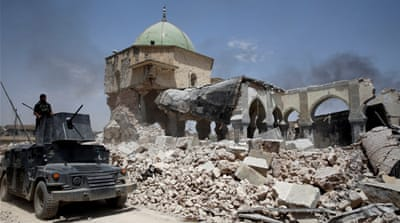 A member of Iraqi forces mans the turret of an armoured fighting vehicle past the ruined Grand al-Nuri Mosque in the Old City in Mosul [Erik De Castro/[Reuters]