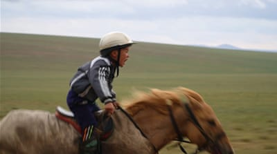 Mongolia's child jockeys risk death to race
