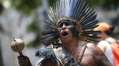An indigenous man sings during a protest against austerity measures in Rio de Janeiro in 2016 [Silvia Izquierdo/AP]