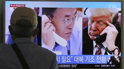 A man watches a television screen showing US President Donald Trump and South Korean President Moon Jae-in during a news programme at the Seoul Railway Station in Seoul, South Korea [AP]