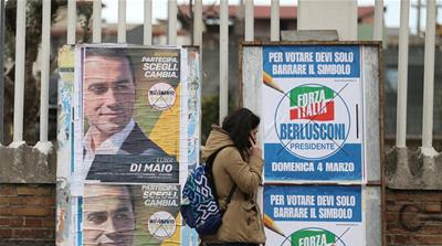 A woman walks past electoral posters of the Five Star Movement's candidate Luigi Di Maio and the Forza Italia party near Naples, Italy, February 21, 2018  [Alessandro Bianchi/Reuters]