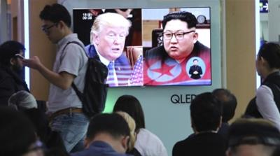 People watch a TV screen showing footage of US President Donald Trump and North Korean leader Kim Jong-un [AP Photo/Ahn Young-joon/Associated Press]
