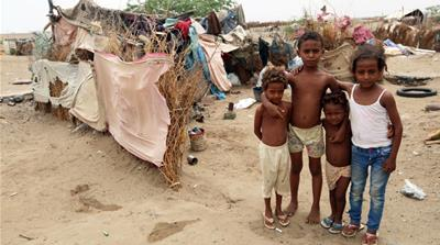 Children pose for a photo outside their family's hut at a shantytown near the port of Hudaida [Abduljabbar Zeyad/Reuters]