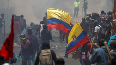 Demonstrators hold Ecuadorian flags as they clash with security forces during a protest against Ecuador's President Lenin Moreno's austerity measures [Carlos Garcia Rawlins/Reuters]