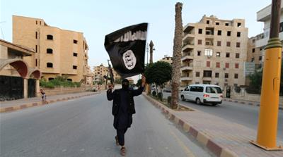 A man waves an ISIL flag in Raqqa, Syria June 29, 2014 [File: Reuters]