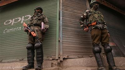 India's Central Reserve Police Force personnel stand guard in front of closed shops in Srinagar [Danish Ismail/Reuters]