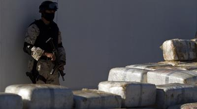 A soldier stands guard next to packages of seized cannabis during a presentation to the media in Tijuana, Mexico, Wednesday, November 3, 2010 [Guillermo Arias/AP Photo]