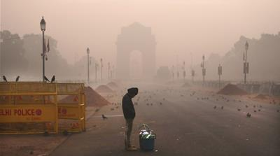 A boy selling tea awaits customers early morning amidst smog on December 26,2018, in New Delhi, India [Manish Swarup/The Associated Press]